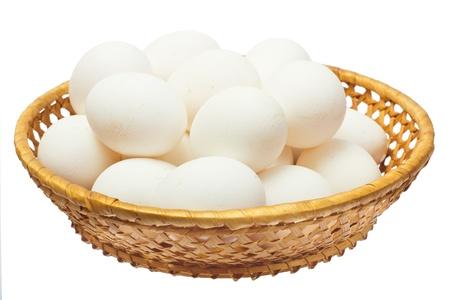 Witte eieren in de mand op een witte achtergrond Stockfoto