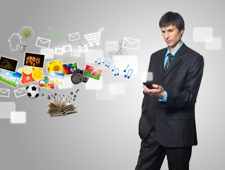 Businessman using mobile phone with touch screen with streaming images, email, multimedia symbols Standard-Bild