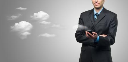 phone button: Zakenman met touch screen telefoon en de wolken op een grijze achtergrond