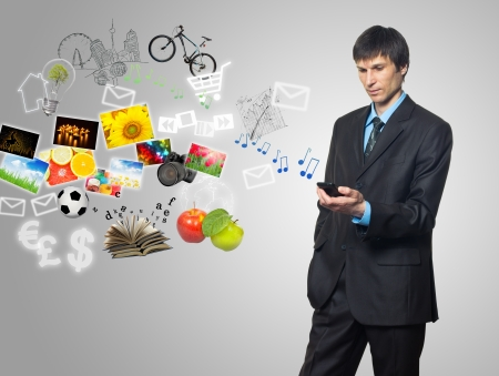 Businessman using mobile phone with touch screen with streaming images, email, multimedia symbols Stock Photo - 13813632