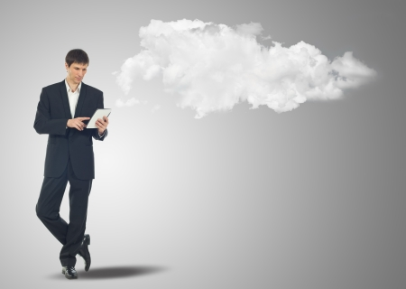 Businessman with touch screen Internet Tablet and the clouds photo