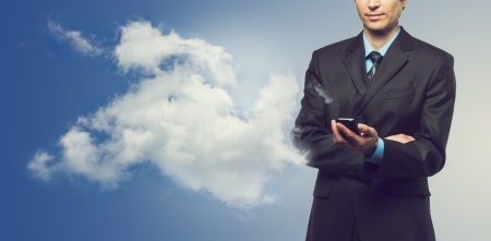 Businessman with touch screen phone and the cloud on blue background photo