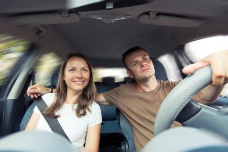 man driving: Pareja joven que monta en un coche Foto de archivo