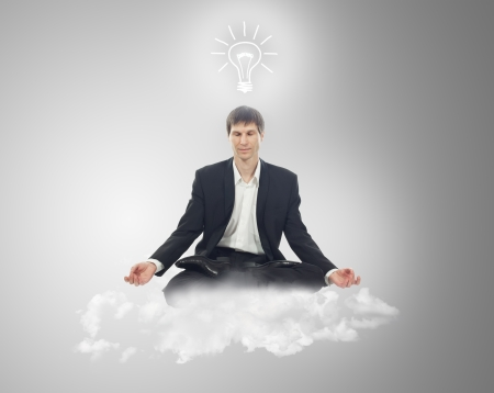 Businessman sitting in lotus position on a cloud with a light bulb over your head photo