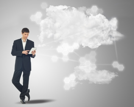 Businessman with touchscreen internet tablet and the clouds on grey background photo