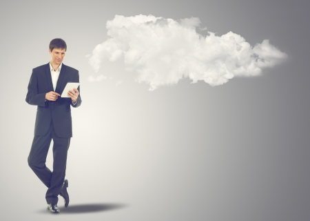 Businessman with touch screen Internet Tablet and the clouds. Maybe will used as concept cloud service photo