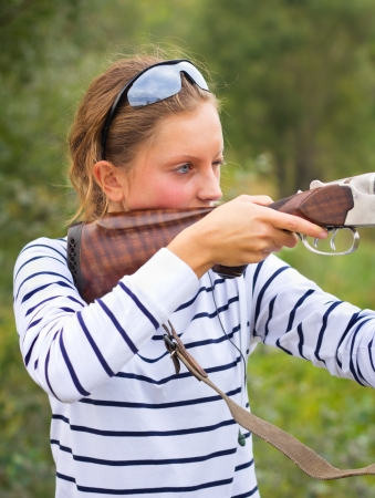A young girl with a gun for trap shooting and shooting glasses aiming at a target photo