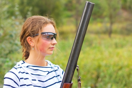 Young beautiful girl with a shotgun in an outdoor photo