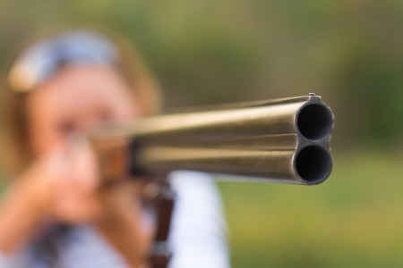 A young girl with a gun and shooting glasses. Short depth of field, focus on the gun barrel