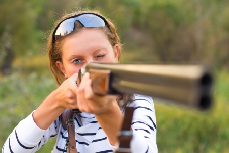 shotgun: A young girl with a gun for trap shooting and shooting glasses aiming at a target