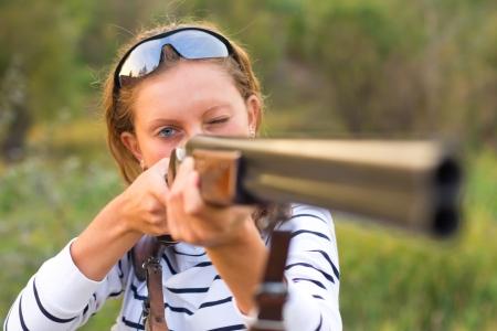 disparos en serie: Una chica joven con un arma para tiro al plato y gafas de tiro apuntando a un blanco