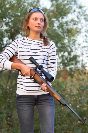 Young beautiful girl in a shooting glasses holding a sniper rifle photo