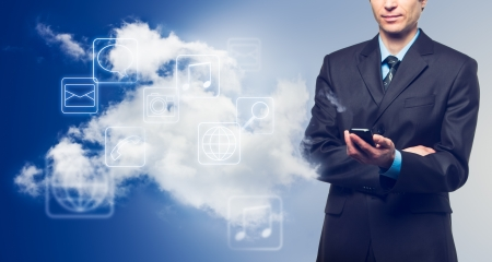 Businessman with touch screen phone and the cloud with icons on blue background Stock Photo - 15174043