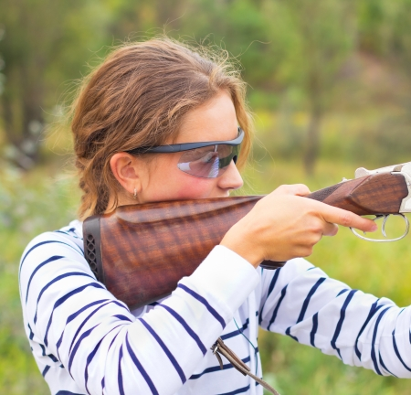 animal trap: A young girl with a gun for trap shooting and shooting glasses aiming at a target