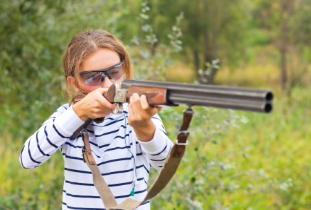 A young girl with a gun for trap shooting and shooting glasses aiming at a target. Short depth of field, focus on the face photo