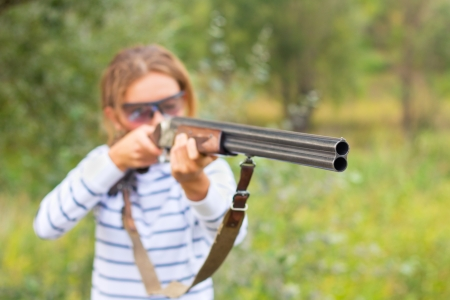 A young girl with a gun for trap shooting and shooting glasses aiming at a target. Short depth of field, focus on the barrel photo