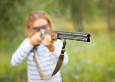 A young girl with a gun for trap shooting and shooting glasses aiming at a target  Short depth of field, focus on the barrel photo