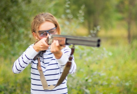 A young girl with a gun for trap shooting and shooting glasses aiming at a target  Short depth of field, focus on the face