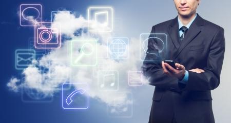 telecomm: Hombre de negocios con tel�fono de pantalla t�ctil y la nube con iconos de aplicaciones en el fondo azul