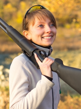 Young beautiful girl with a shotgun in an outdoor Stock Photo - 15812451