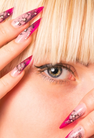 Young beautiful blonde with a nice manicure. Focus on eyes photo