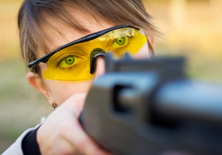 A young girl with a gun for trap shooting and shooting glasses aiming at a target Stock Photo - 16037115