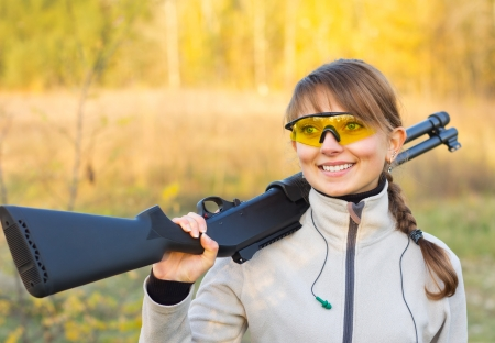 Young beautiful girl with a shotgun in an outdoor Standard-Bild