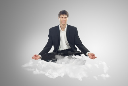 Businessman sitting in lotus position on a cloud photo