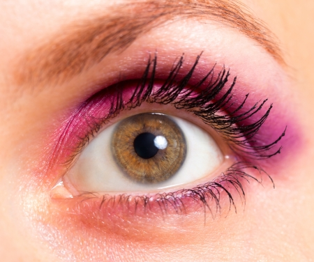 Close-up woman's beautiful brown eye with bright pink and violet makeup photo