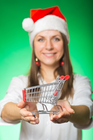 Cheerful girl in a Christmas hat with cart on a green background photo