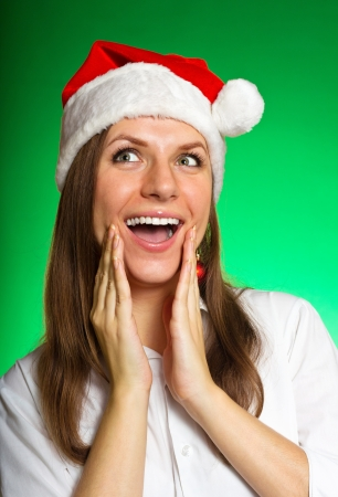 Cheerful girl in a Christmas hat on a green background photo