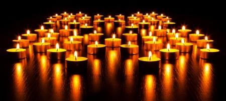 luz de velas: Panorama de las muchas velas ardientes con profundidad de campo