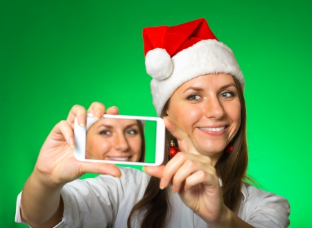 Cheerful girl in a Christmas hat with cellphone makes a photo on a green background photo