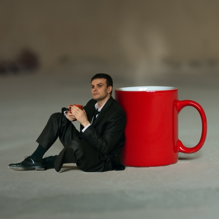Concept  Businessman with a cup of tea sitting around a large cup in thought photo