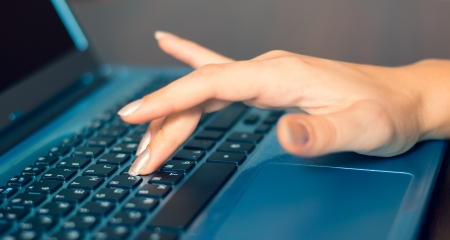 Closeup of typing female hands on laptop photo
