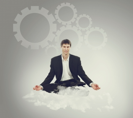 Businessman sitting in lotus position on a cloud and think mechanical thoughts Stock Photo - 16694601