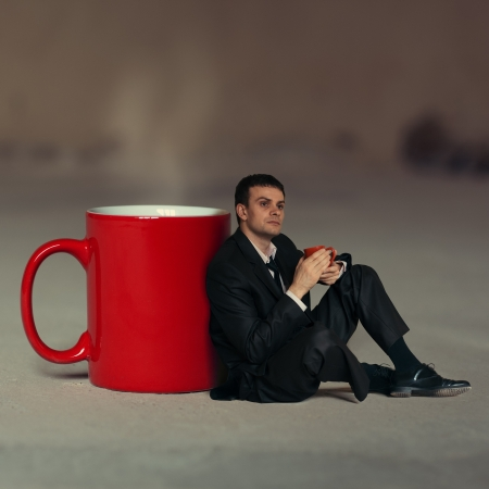 Concept  Businessman with a cup of tea sitting around a large cup in thought Stock Photo - 16764978