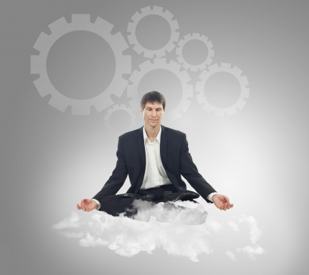 Businessman sitting in lotus position on a cloud and think mechanical thoughts Stock Photo - 16764925