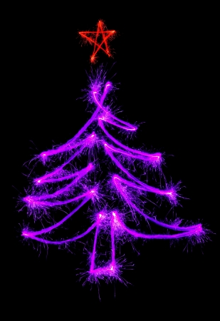 Christmas tree made by sparkler on a black background photo