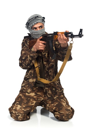 Terrorist Arab nationality in camouflage suit and keffiyeh with automatic gun on white background with reflection