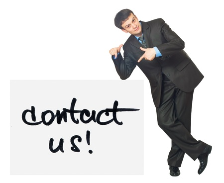 Young businessman points on a card Contact Us on a white background photo