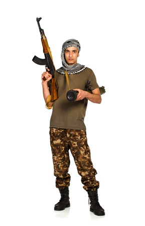 Terrorist Arab nationality in camouflage suit and keffiyeh with automatic gun and launcher on white background with reflection photo