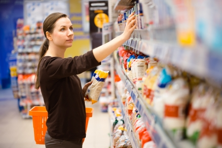 grocery stores: Beautiful young woman shopping for cereal, bulk in a grocery supermarket