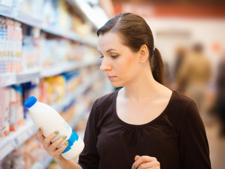 Beautiful young woman shopping for milk in a grocery supermarket