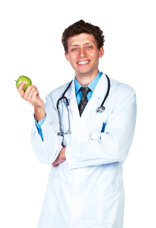 Portrait of a smiling male doctor holding green apple on white background photo