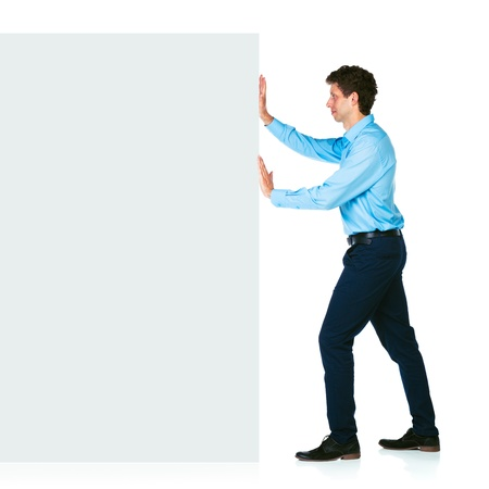Young businessman pushing a blank billboard on white background photo