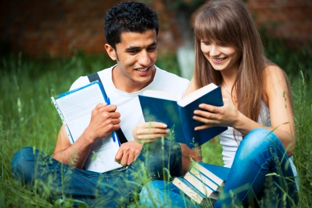 Two students guy and girl studying in park on grass with book outdoors photo