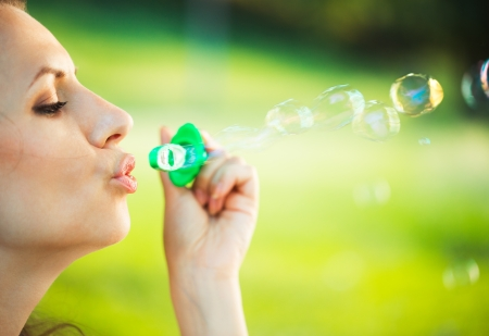 Close-up portrait of a girl blowing soap bubbles in the park photo