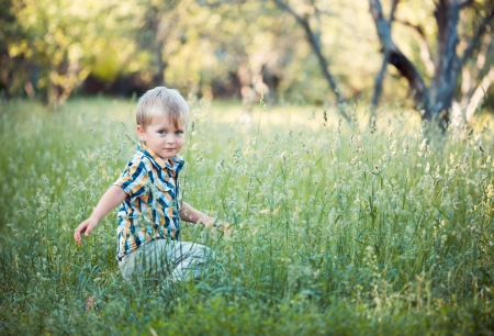 A cute little baby boy sit in the grass in park photo