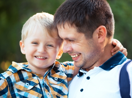 familias unidas: Feliz padre y su hijo beb?ue se divierten en el parque al aire libre